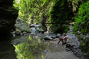 A lady walker rests after negotiating moderate terrain in the rocky gorge near the 15m high Kozjak Waterfalls, part of the Kobarid Heritage Trail, on 21st June 2018, in Kobarid, Slovenia.