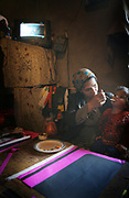 Marzia, 46, the first wife of Noor Agha, about 52, feeds her daughter Alisa, 2, as she makes a kite in the house, Kabul, Afghanistan, Saturday, March, 10, 2007. Noor Agha is a renowned kite maker who made kites for the movie makers of the best-selling novel, The Kite Runner, which will be distributed by Dreamworks and Paramount Vantage in Nov. this year. Noor Agha's wives, using their special glue, help him produce enough kites to please the clients' needs. Some of his children can also make their own kites with plastic bags and bamboo sticks. As the Afghan New Year's Day (Nawruz) approaching on March 21, the finger tips of Noor Agha's family got busier for mass production.