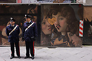 Carabinieri officers mingle with crowds and patrol the darker covered galleries and streets around Florence's Piazza degli Uffizi. In front of them reproductions of renaissance painting that now adorns a construction hoarding screen. Watching for suspicious activity as well as playing cat and mouse from illegal street hawkers selling fake goods and copyrighted artwork prints, we see an incongruous landscape of classical art and urban modernity. Someone has drawn a moustache and cannabis joint in the mouth of a religious character as the two policemen keep the city secure from possible attack.
