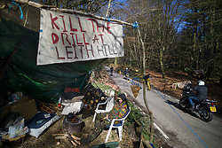 © Licensed to London News Pictures. 02/03/2017. Coldharbour, UK. A protestors sits under a sign reading 'KILL THE DRILL AT LEITH HILL' at the 'Protection Camp' on Leith Hill. Activists have constructed and occupied a fort and some trees on the site of a proposed oil well. Planning permission for 18 weeks of exploratory drilling was granted to Europa Oil and Gas in August 2015 after a four-year planning battle. The camp was set up by protestors in October 2016 in order to draw  attention to plans to drill in this Area of Outstanding Natural Beauty (AONB) in the Surrey Hills. The camp has received support from the local community.  Photo credit: Peter Macdiarmid/LNP