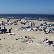 NLD/Bloemendaal/20100604 - Mensen liggend op het strand van Bloemendaal, genietend van de zon