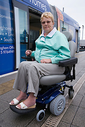 Portrait of woman wheelchair with tram in the background,