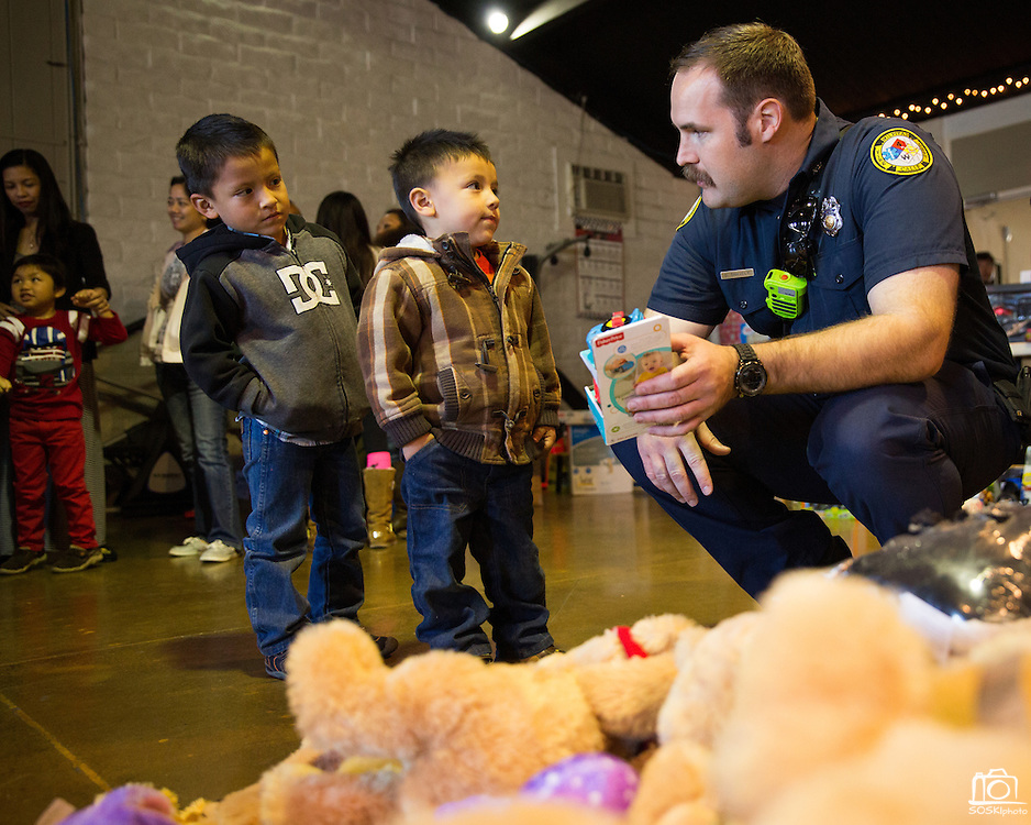 David Snavely of Milpitas Fire Station 4 helps brothers Edgar Mireles, 5 (left), and Jhonefe, 3, select toys for Christmas during a Milpitas Fire Department toy drive at Genesis United Methodist Church in Milpitas, California, on December 21, 2013. (Stan Olszewski/SOSKIphoto)