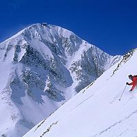 Big Sky ski area, Big Sky, Montana.Skier descends steep powder in front of 11,166 foot Lone Mountain.
