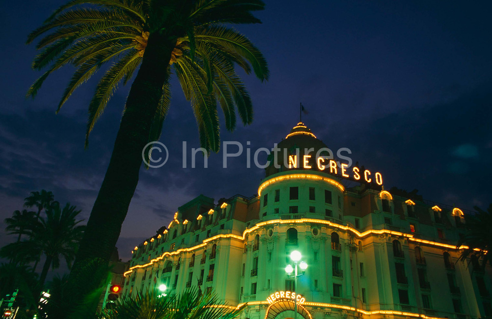 From a low angle looking upwards to the building exterior of the Hotel Negresco on the Promenade de Anglais, Nice. We see the colourful orange light bulbs and the overall green hue from sodium illumination and the blue of the evening sky. In the foreground is an example of the ubiquitous palm trees that line the Côte d'Azur. The Hotel Negresco on the Promenade des Anglais on the Baie des Anges in Nice, France was named for Henri Negresco (1868-1920) who had the palatial hotel constructed in 1912. Noted for its doormen dressed in the manner of the staff in 18th-century elite bourgeois households, complete with red-plumed postilion hats, the hotel also offers renowned gourmet dining at Le Chantecler. In 2003 the Hotel Negresco was listed by the government of France as a National Historic Building. Nice is a major tourist centre and a leading resort on the French Riviera. Located in the Provence-Alpes-Côte d'Azur région, it is a commune and the préfecture (administrative capital) of the Alpes-Maritimes département.