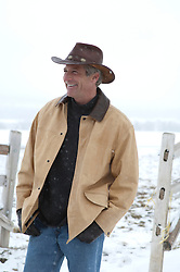 smiling cowboy on a ranch in the winter