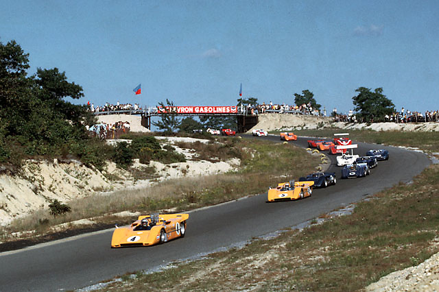First Lap through Turn One at the old Bridgehampton circuit. Bruce McLaren leads Denny Hulme in their McLaren-Chevy M8s, with Peter Revson's Shelby American McLaren-Ford M6B on their heels. Eventual winner Mark Donohue is fourth in line here in his Penske McLaren M6B Chevy with Dan Gurney's McLeagle right behind. There are two winged cars, Jim Hall's Chaparral and John Surtees in a Lola.