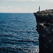 Woman standing on the edge of a large cliff overlooking the ocean. Taken in the Bahamas.