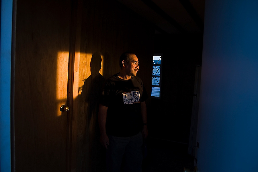 A man watches the sun set from inside his home at Hudson Valley Foie Gras in Ferndale, New York on October 11, 2008. Some of the workers and their families, practically all Mexican immigrants, live on the grounds of the factory in company provided housing; a small, isolated Mexican community flourishes in the Catskills.