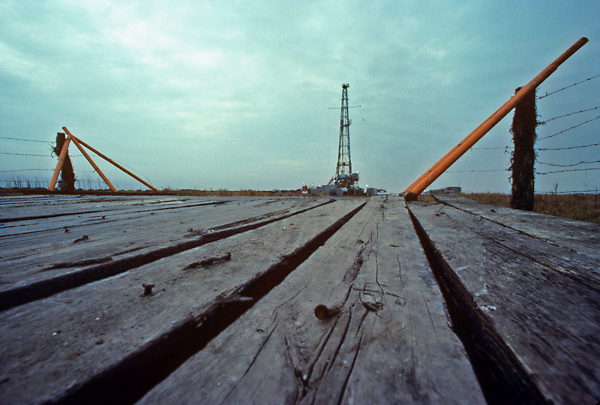 Stock photo of an on-shore oil and gas drilling rig from a plank wood covered road