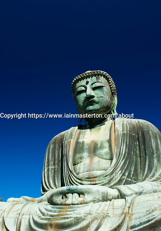 Detail of famous outdoor bronze Buddha statue at Kamakura in Japan