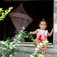 South America, Brazil, Amazon. A baby sits in a window of an Amazon river home.