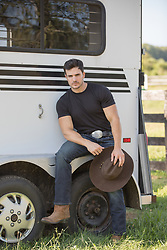 hot cowboy sitting on the back of a horse trailer