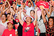 """10 MAY 2010 - BANGKOK, THAILAND: Thai Red Shirts cheer upon hearing that their leaders have accepted the government terms for ending the protest during a Red Shirt meeting Monday night. The Red Shirt leaders met with their supporters Monday evening and specified the terms for ending their protest in Bangkok and occupation of the Ratchaprasong Intersection in the heart of the Thai capital's shopping district. The accepted the Prime Minister's """"Road Map for Reconciliation"""" and added one condition, that Thai Deputy Prime Minister Suthep Thaugsuban turn himself into police for his role in allegedly ordering the security forces attack on Red Shirts protestors on April 10 that resulted in more than 20 deaths and 800 injuries. Late Monday night Suthep said he would meet with police Tuesday morning. The Red Shirts haven't confirmed if that meets their demand, so the status of the protest is unknown.   PHOTO BY JACK KURTZ"""