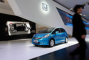 A visitor walks past a GAC Honda Fit t on display at the 8th China (Guangzhou) International Automobile Exhibition in Guangzhou, China, on Monday, 20 December 2010. Automakers from across the world are increasingly focusing their efforts on China, the largest auto market in the world and the only major market with prospects of high growth rate.
