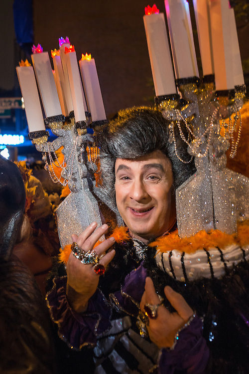 New York, NY, October 31, 2013. A man dressed as pianist Liberace, with candelabras on his shoulders and huge rings on his fingers in the Greenwich Village Halloween Parade.