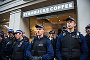 London, UK. Wednesday 19th November 2014. Student Assembly Against Austerity demonstration in protest at education spending cuts, tuition fees, and the resulting students debt. Police lines outside Starbucks.