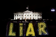 Protestors hold up a lighted sign as a demonstration against U.S. President Donald Trump outside the White House in Washington.   REUTERS/Jim Young