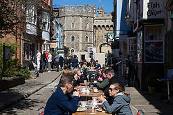 Windsor, UK. 17th April, 2021. Visitors sit at tables outside a restaurant close to Windsor Castle on the day of the funeral of the Duke of Edinburgh. The funeral of Prince Philip, Queen Elizabeth II's husband, is taking place at St George's Chapel in Windsor Castle, with the ceremony restricted to 30 mourners in accordance with current coronavirus restrictions.