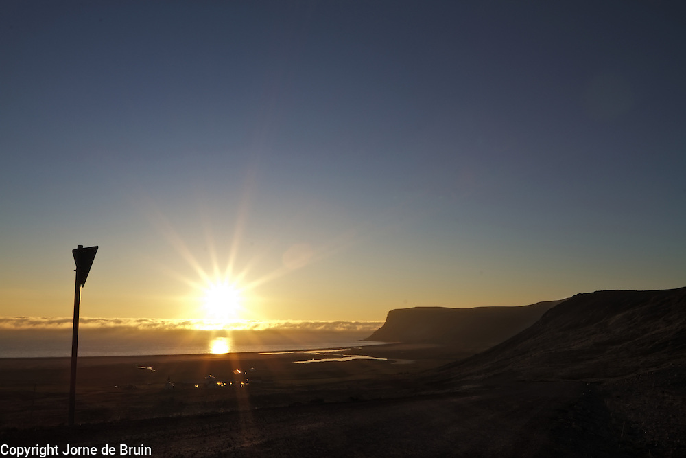 The sun is shingn over the village of latrabjarg at midnight in Iceland.