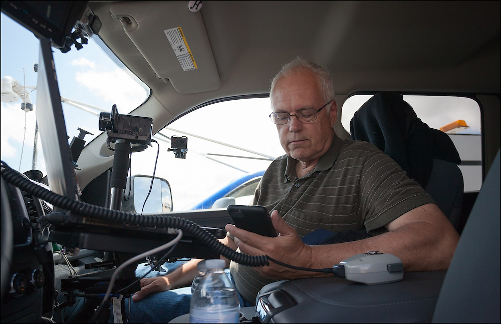 Tim Marshall looking over weather data on his phone while working with the Center for Severe Weather Research team on the TWIL project.