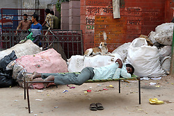 One man and his dog rest near Chandni Chowk metro station (note the neat placing of the shoes) in Delhi India.  The Commonwealth Games are being held in Delhi India between the 3rd and 14th October 2010..Photoby:  Ron Gaunt/SPORTZPICS