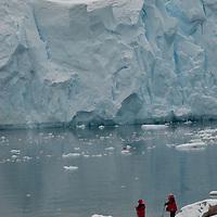 Tourists stand below a huge glacier front at Neko Harbor, Antarctica.