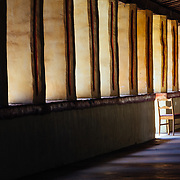 A lone chair sits in the exterior halls of the Carmel Mission Basillica near Monterey, California.