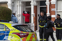 A postman delivers mail to the flat where a 'small, contained' fire in Burnfoot Avenue, Fulham, claimed the life of a woman. Fulham, London. February 07 2018.