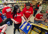 """Kiara Dame and Dante Parker place stickers on alcoholic beverage packaging at Vista Foods as part of the """"Sticker Shock"""" program with Stand Up Laconia and Laconia Middle School 8th graders.  (Karen Bobotas/for the Laconia Daily Sun)"""