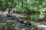 Women balancing over rocks and logs, crossing a stream near Porva-Csesznek, Veszprem, Hungary.