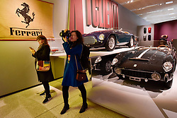 """© Licensed to London News Pictures. 14/11/2017. London, UK.  Visitors in front of (L to R) a Ferrari 250 GT Cabriolet, 1957, and a Ferrari 166 MM, 1950. Preview of """"Ferrari: Under the Skin"""", an exhibition at the Design Museum to mark the 70th anniversary of Ferrari.  Over GBP140m worth of Ferraris are on display from private collections including Michael Schumacher's 2000 F1 winning car.  The exhibition runs 15 November to 15 April 2018.  Photo credit: Stephen Chung/LNP"""