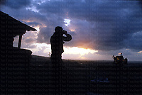 A British army soldier on sentry alongside a mounted GPMG at sunset in Beirut December 1983. 'Officers call' was played by trumpet every evening at British forces HQ. Photograph by Terry Fincher