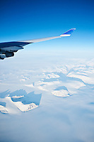View out airplane window of wing and snow covered mountains of Greenland