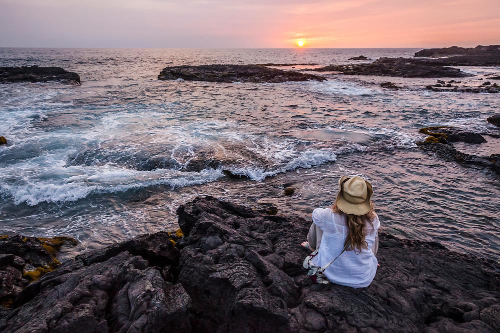 Woman sits on old lava rocks at waters edge watching the sunset, Wawaloli Beach Park, Kailua-Kona, Hawaii, USA.