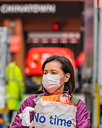 No time - Tourists and locals mask up as they wander the quieter streets of China Town - Anti Coronavirus (Covid 19) defences, wearing inefectual masks in London.