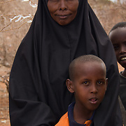 A proud mother waits for relief distribution with her son during the East African drought. Wajir, North Eastern Province, Kenya.
