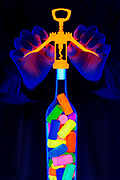 A wine bottle filled with glowing corks is opened with a wing style bottle corkscrew. Blacklight photography.