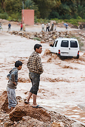 Young boys observing river crossing during flood at Ait Snan on road to Todra Gorge, Morocco.