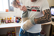 A prisoner puts on his home made boxing gloves that are used for training. HMP/YOI Portland, Dorset, United Kingdom.