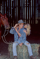 cowboy and girl in a barn with a horse horsing around