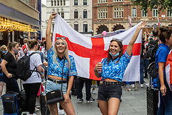Licensed to London News Pictures. 11/07/2021. London, UK. England fans Louanne Gibson 24 and Charley Sargent 22 from Kent wave flags in Leicester Square, London ahead of England's Euro 2020 finals match. England take on Italy in the Euro 2020 final at the iconic Wembley Stadium this evening. Photo credit: Alex Lentati/LNP