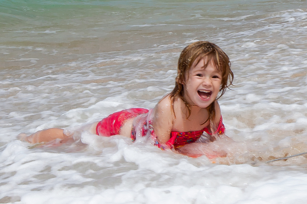 A little girl laughs in delight on a boogie board on the beach in Hawaii