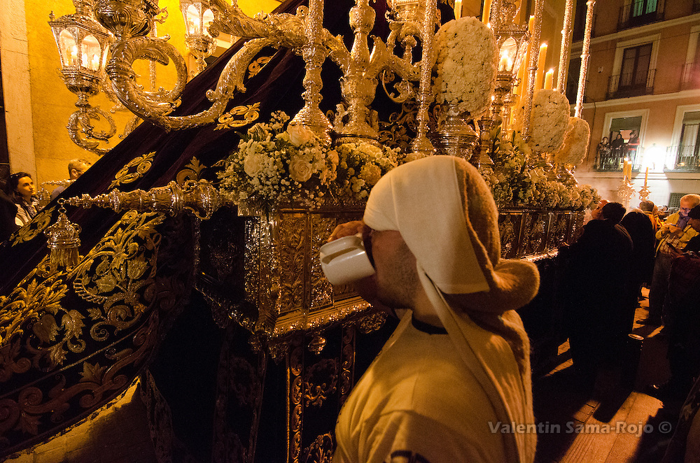 'Costalero' drinking water during of of the stops of the float of virgin 'Maria Santisima Inmaculada Madre de la Iglesia' during Palms Sunday procession in Madrid.