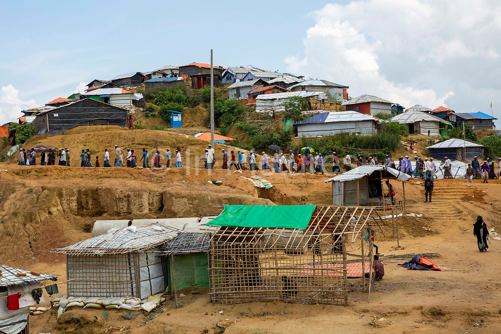 Men walk along the dirt path as part of a funeral procession within the Kutupalong refugee camp outside Cox Bazar, Chittagong Division, Bangladesh, Asia. The rapid influx of the Rohingya people into the refugee camp has led it to be called the largest slum in the world.