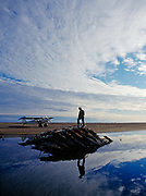 Cape Smythe Air pilot Glenn Hittson inspecting century old wreck of whaling ship on spit of Point Franklin north of Peard Bay, Arctic Ocean, Piper PA18 Super Cub on beach beyond, Alaska.