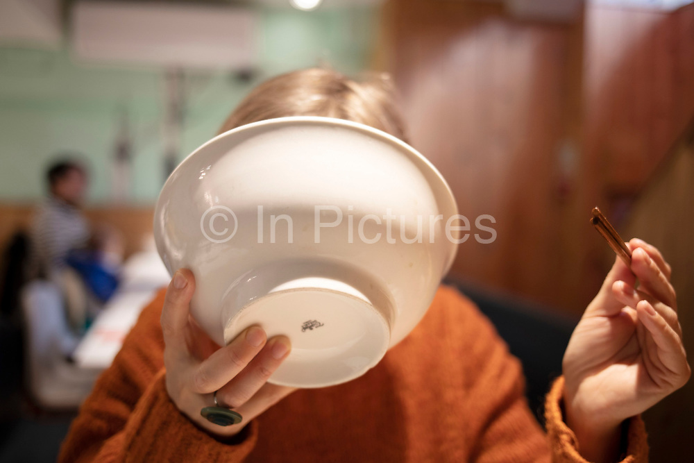 Woman tipping a bowl to her face drinking the remainder of her ramen broth soup in a restaurant in London, United Kingdom.