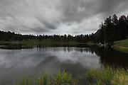 Perfect reflections of the dark clouds in Trout Lake in Yellowstone National Park's Lamar Valley