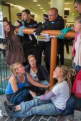 © licensed to London News Pictures. London, UK 19/08/2013. Police officers trying to move a group of anti-fracking protesters who superglued themselves to the entrance of Bell Pottinger PR company in Holborn, London to protest against the fracking in Balcombe. Photo credit: Tolga Akmen/LNP