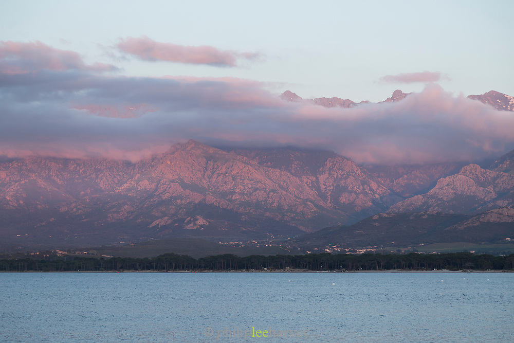 View of mountains and sea under cloudy sky, Calvi, Corsica, France